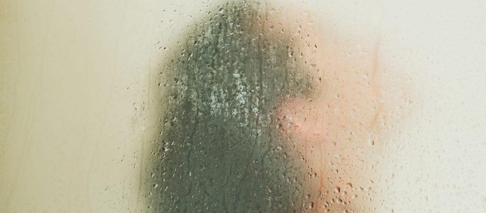 Woman washing behind weeping glass shower door