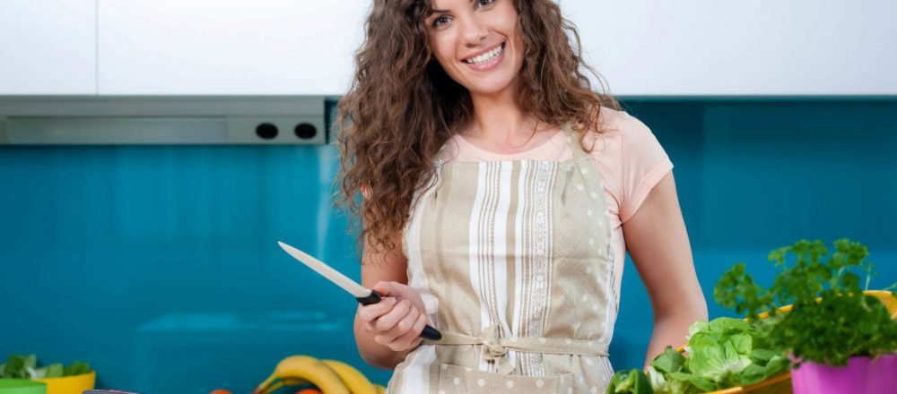 Young woman cooking in the kitchen healthy food, vegetable Salad. Holding a knife and cutting vegetables on a cutting board. Healthy lifestyle cooking at home.